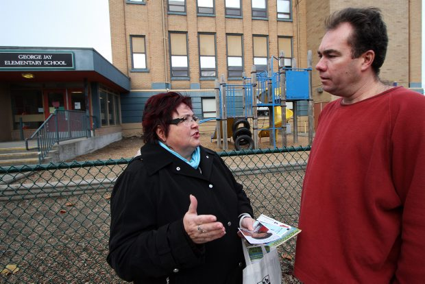 Candidate Edith Loring-Kuhanga talks with parent Jon Franta outside George Jay Elementary School Wednesday.