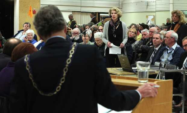 A speaker addresses Mayor Christopher Causton, whose back is to the camera in this photograph, and other members of the outgoing Oak Bay council during Monday's spirited public meeting at the packed Monterey Centre.