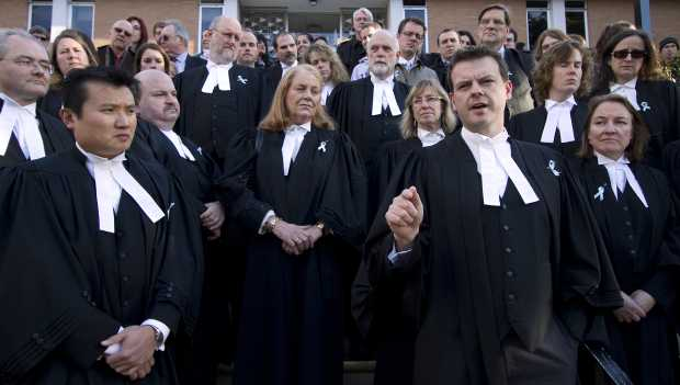 Paul Pearson, second from right at the front, speaks during the lawyers' rally in Victoria Wednesday.