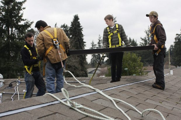 Left to right, Edward Hale, Steve Planes, Cameron Sinclair, and Daniel Justensen install a solar panel in Colwood Wednesday.