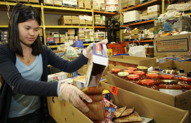 Quinn Willson sorts through food Tuesday at the Mustard Seed Food Bank, now distributing holiday-season hampers.