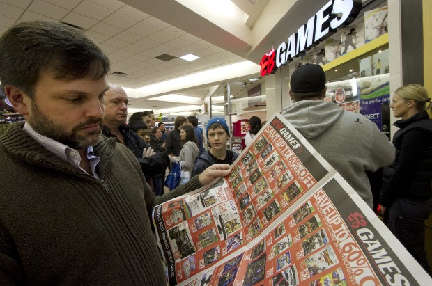 Shopper John Stevens checks out at Boxing Day deals Monday outside EB Games in the Mayfair Shopping Centre.