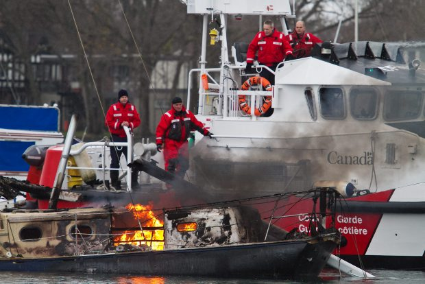 Canadian Coast Guard Auxiliary members watch over the burning remains of Fritz Schreiner's boat home Thursday.