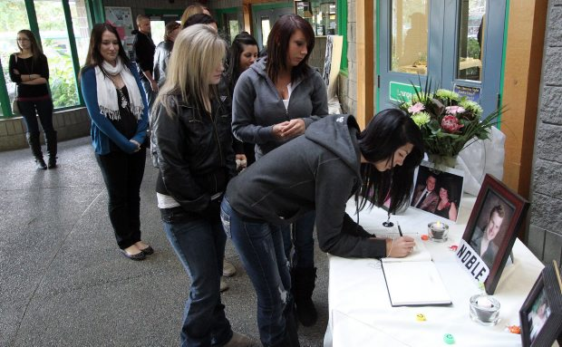 People sign the guest book during a memorial at the Shawnigan Lake Community Centre for Tyler Noble, 20, one of six homicide victims last year. (Dec. 2011)