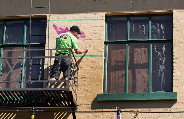 A worker removes graffiti from above Shanghai City on Fisgard Street in Victoria on Aug. 3, 2011. Victoria police say graffiti removal in communities throughout the Capital Regional District costs about $1 million a year.