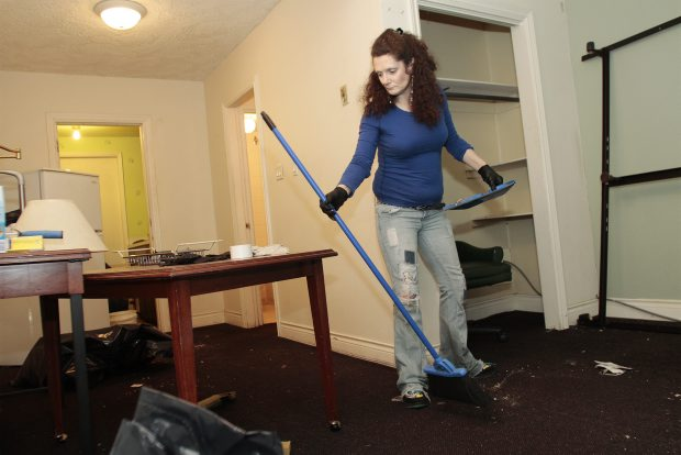 Bonnie Frederick cleans the living area of a room at the Queens Manor.
