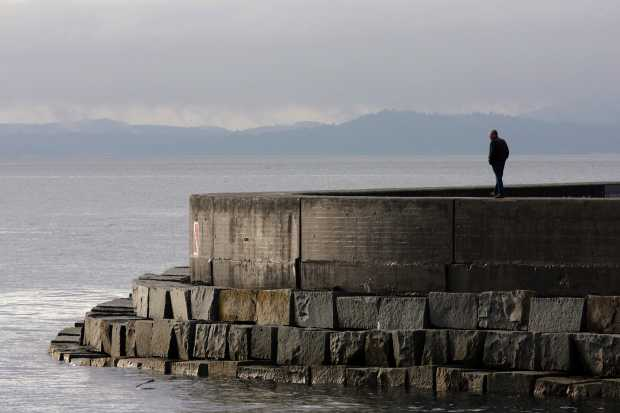 A man walks at Ogden Point during a recent king tide, a phenomenon that produces high water levels. Scientists at a weekend conference said communities should introduce measures that are able to cope with a rise in sea levels.