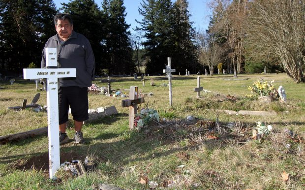 Frazer Smith Sr. at his son's grave, from where the totem was stolen this week.