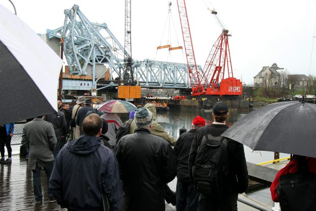 People gather to see the largest ocean-going crane on the West Coast remove the rail span Friday.