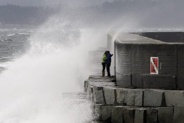 Storm watchers brave the waves at Ogden Point on Tuesday.
