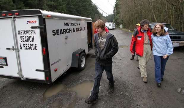 Search manager Craig Barlow hugs Debbie Abraham as her son Russell, left, walks at the Metchosin Search and Rescue command centre on Sooke Road Sunday, March 4, 2012.
