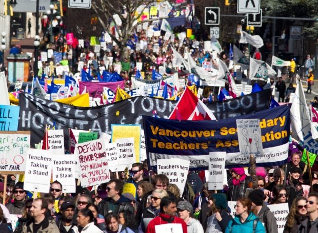 Demonstrators march down Government Street to a B.C. Teachers Federation and B.C. Federation of Labour rally at the B.C. legislature