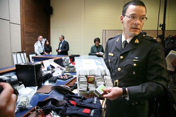 Burnaby RCMP Insp. Tim Shields shows off some of the items police seized in a Metrotown condo that they believe is part of a massive identity theft ring.