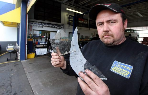 Scott Harrison holds shards of glass from a broken window at his shop on Douglas Street. Harrison wants police to respond to problems of people abandoning shopping carts and vandalizing and fouling his property.