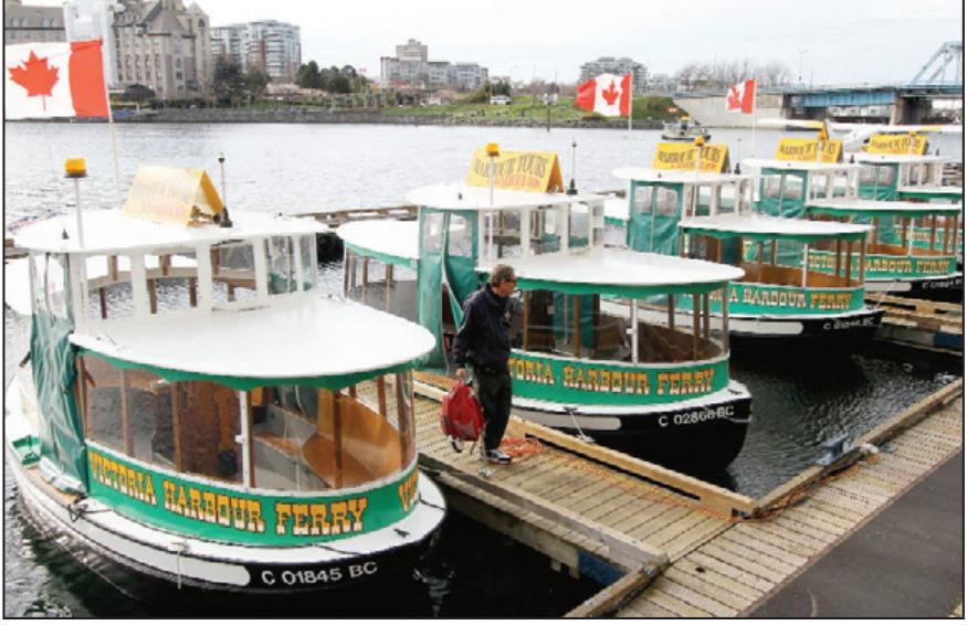 Boat operator Dave Knowlton walks Sunday among Victoria Harbour Ferry boats docked in the Inner Harbour after vandalism.