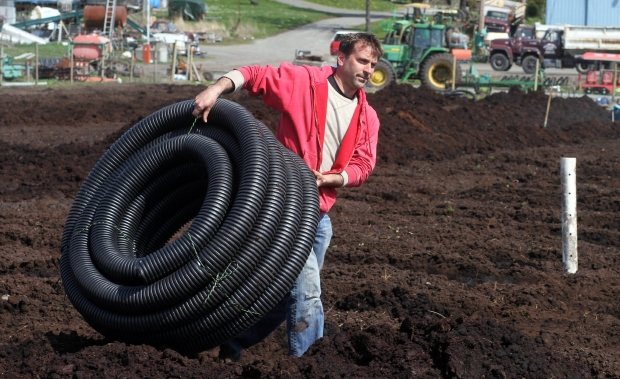 Rob Galey works to improve drainage at one of his fields off Blenkinsop Road in Saanich