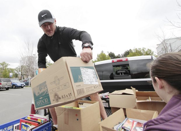 Todd Fitzsimmons unloads books donated by Christ Church Cathedral School for the Times Colonist book sale on Saturday. The drive continues today at the curling club.
