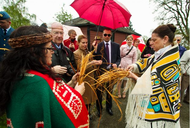 Debbie Hunt, left, and Gwen Gold hand out cedar shavings at a traditional blessing to mark the beginning of a new 30-foot totem pole being carved on the Government House grounds