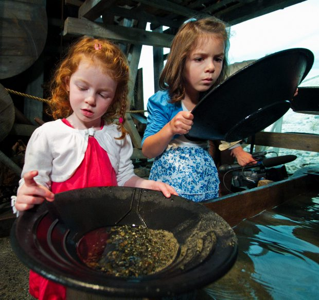 Three-year-old Peyton Ross, left, and five-year-old Ainsley Ross pan for gold Tuesday at the Royal B.C. Museum as part of a government announcement about Family Day.