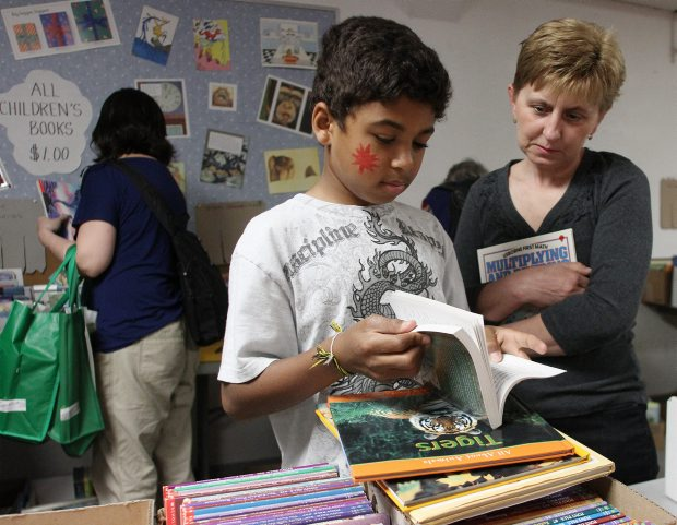 Damian Hliwa (left), 11, and his mother Yolanda check out some of the books during the TC book sale at the Victoria Curling Club.