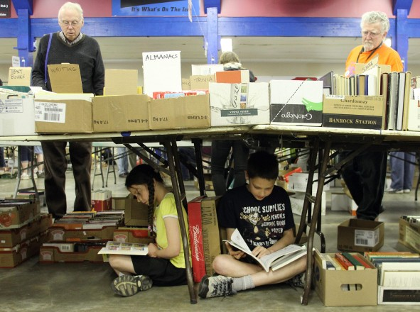 Briana, 8, and her brother Alex Wright, 11, find a comfortable place to read during the Times Colonist Book Sale at the Victoria Curling Club on Sunday, May 13, 2012.