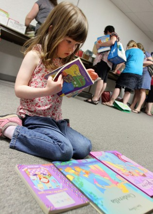 Emma Lorimer, 3, is absorbed during the Times Colonist Book Sale at the Victoria Curling Club on Sunday, May 13, 2012.
