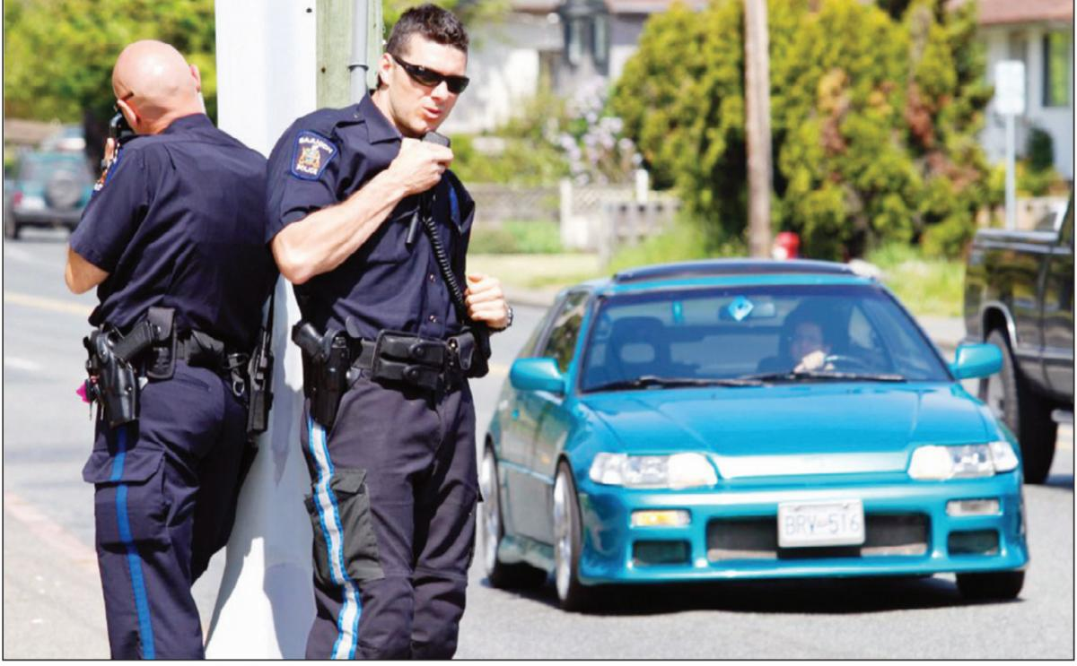 Saanich Police Const. Richard Burdett, left, and Const. Cory Scott monitor traffic at the Quadra Street-McKenzie Avenue intersection on Tuesday.
