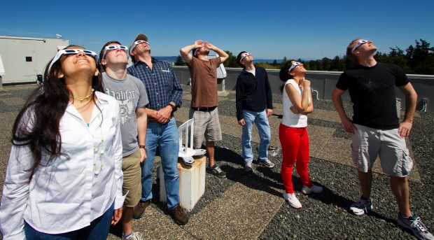 University of Victoria astronomy grad students, left to right, Athira Menon, Michael Palmer, instructor Russ Robb, Masen Lamb, Chris Barber, Azadeh Fattahi and Andy Pon, look at the sun using Eclipser glasses.