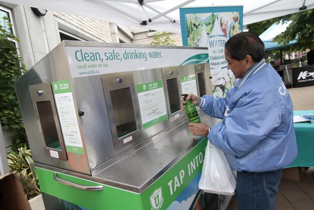 Danny Cecilio fills a bottle with CRD tap water from its cart at Centennial Square.