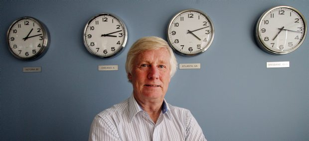 Warren Brown in his Procura office, with clocks showing the time around the world.
