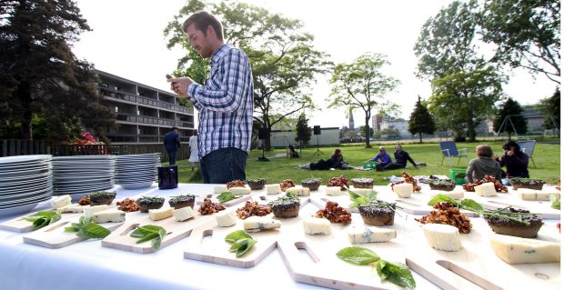 Eric Nordal collects a platter of food for one of the participants in Tuesday's picnic.