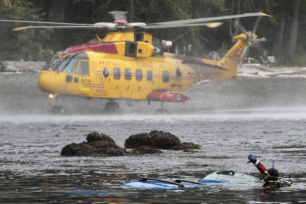 A helicopter crew assists divers recovering the body of a woman whose car went into the ocean in the Sooke area on Wednesday. RCMP said the woman was driving down the steep driveway of her waterfront home on West Coast Road when the car went out of control.