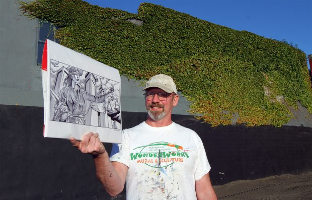 Artist Steve Milroy holds a drawing of Lady Justice that will form a mural for the brick wall behind him.