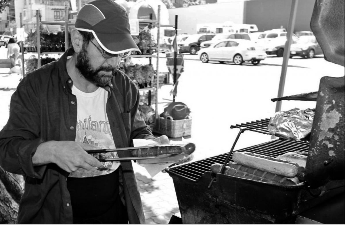 David Esbati serves up a hot dog from his Mr. Tube Steak food cart at the corner of Store and Chatham streets.