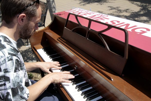 Adam Mahoney plays on the Make Me Sing piano at Fisgard and Douglas.
