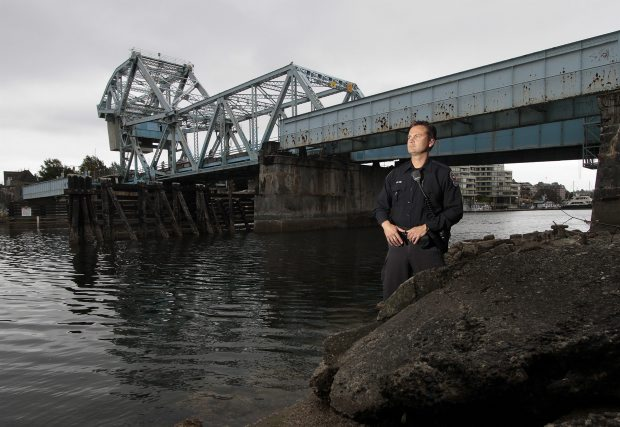 Victoria Police Const. Mark Jenkins stands near the spot where he dove into the chilly harbour waters to rescue a man who had jumped from the Johnson Street Bridge.