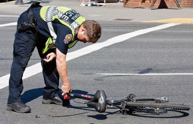 Police investigate after a bicyclist collided with a truck near the corner of Douglas Street and Burdett Avenue on Thursday.
