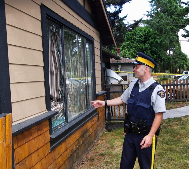 West Shore RCMP Const. Scott Rothermel shows the window he broke Friday to enter a burning Colwood house and rescue a dog.