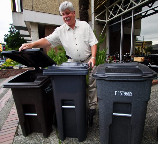 Terry Snow, who heads the city's recycling program, displays bins for the kitchen scraps and garbage program.