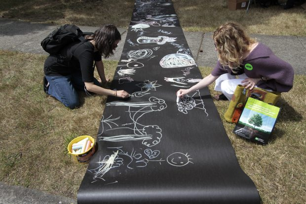 Jo Sargeant, left, and Sarah Bonsur Kurki add to painter/sculptor Jeremy Gordaneer's chalk art at the TD Art Gallery Paint-In on Moss Street on Saturday. Thousands of visitors and 150 artists took part in the art demonstration, now in its 25th year.