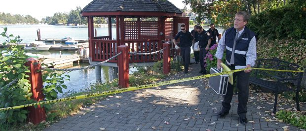 Coroner Larry Crawford holds the police tape as the body of a 75-year-old man is carried up the path at the Gorge Pointe condominiums on Saturday.
