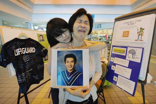 Mabel Chan holds a photo of her son, Leo Chan, and is comforted by his friend, Alexia Tang. Leo, a University of Victoria student, died in January of meningitis.