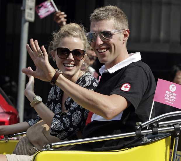 Cyclist Ryder Hesjedal and his wife Ashley ride in a pedicab to homecoming celebrations at Centennial Square on Friday.