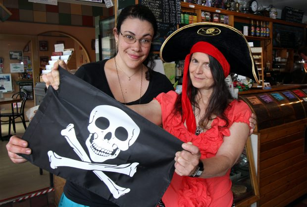 Kayt Mills, left, and Kim Willoughby hold a pirate flag like the one that has gone missing from the James Bay Coffee Shop.