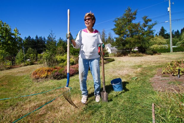 Garden Gate Road resident Maya Brouwer keeps a pitchfork handy while gardening on Aug. 24, 2012, because of cougar sightings in her Central Saanich neighbourhood area.