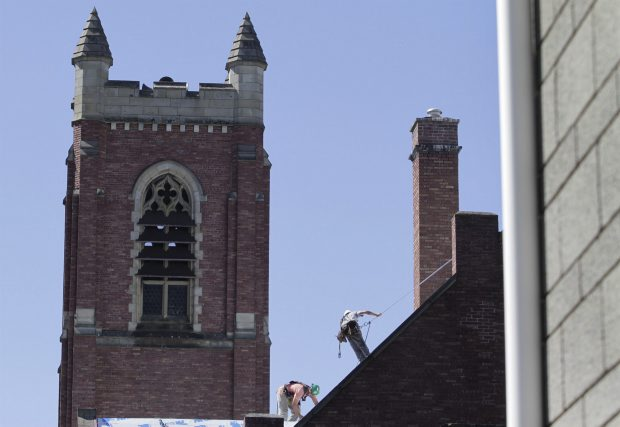 Workers replace the roof on the First Metropolitan United Church on Quadra street.