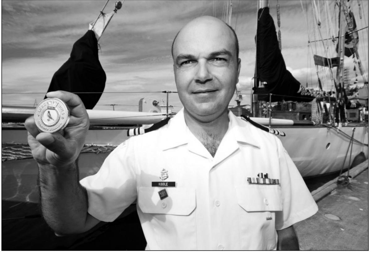 Lt.-Cmdr. Jeff Kibble shows the special-edition commemorative coin cast with the ship's original brass to celebrate the Diamond Jubilee of HMCS Oriole.